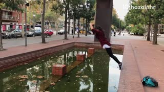 Black red flannel girl parkour falls into fountain - Video