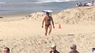 Guy in blue speedo balancing surfboard at beach - Video