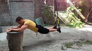 Strong muscular guy workout with trx