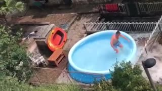 Guy records friend jumping into blue blow up pool in backyard home breaks pool water spills - Video