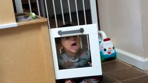 Toddler makes funny squished faces against a window