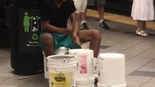 Guy in black shirt plays drums on buckets