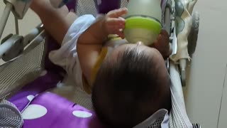 An 8-month-old baby holds a bottle of super cute milk