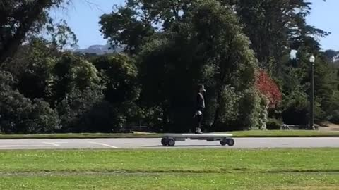 Girl at golden gate park rides a huge motorized skateboard