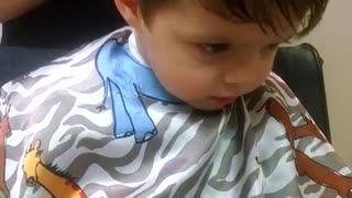 Toddler struggles to stay awake during haircut - Video