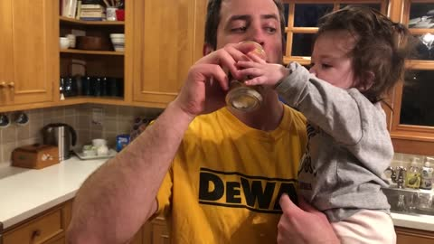 Baby girl is desperate for a sip of daddy's drink