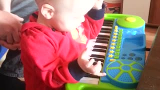 Little boy falls playing toy piano