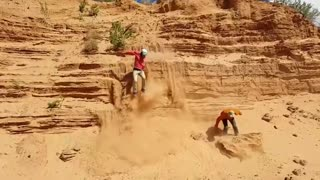 Two guys try to get down of a sand cliff - One fails