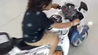 Little girl driving white toy motorcycle falls down