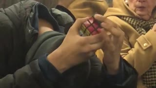 Guy does rubik's cube with head down without looking on subway train