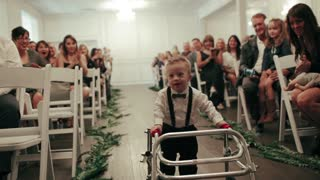 Boy with Down Syndrome walks aisle as ring bearer