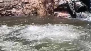 Slo-mo video guy slides down small waterfall