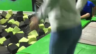 Guy slips and fails at green trampoline park - Video
