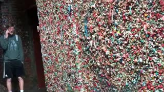 Guy blue sweater licks seattle gum wall