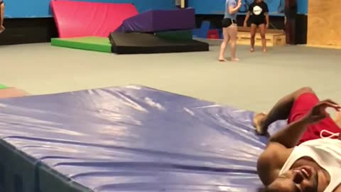 Guy red shorts misses trapeze front flip falls on blue floor