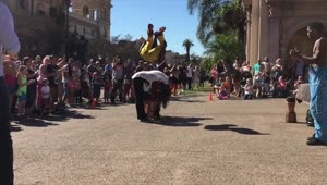 Street performer front flips over 4 people - Video