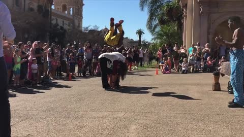 Street performer front flips over 4 people