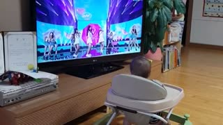 Baby has hilarious reaction to singers on TV - Video