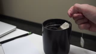 Teabag being dipped in a cup of tea