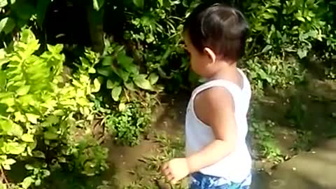 Toddler attempts to befriend his own shadow