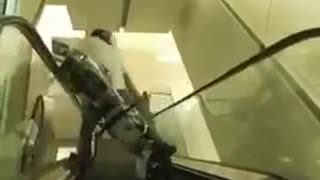 Guy riding bike down escalator second angle