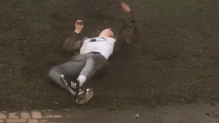 Guy in brown jacket rolling down hill