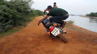 Wonderful bullet motor bike stunt on the side of canal by young generation  - Video