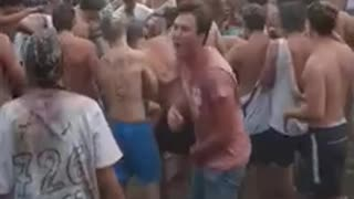 Shirtless guy carried by crowd falls down - Video