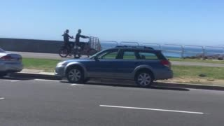 Two guys on wetsuits ride tandem bikes - Video