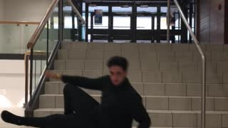 Guy in black sweater slides down stairs
