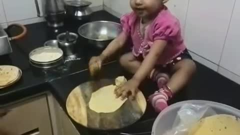 little baby making food (roti)