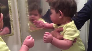 Baby girl attempts to make contact with her mirror reflection - Video
