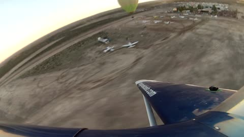 Stunt planes surround hot air balloon during takeoff