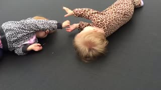 Precious identical twins play together with their hands