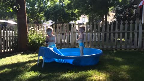adorable twins having fun in the pool