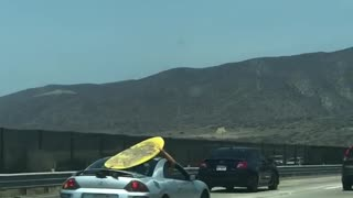 Yellow surf board on grey silver car roof - Video
