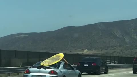 Yellow surf board on grey silver car roof