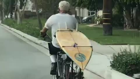 Old man white hair driving bike with surfboard in back