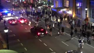 Police SUV runs through crowd crossing the street