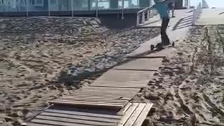 Guy longboard skateboard down wood pier sand falls over - Video