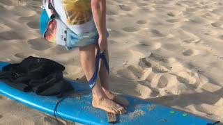 Guy blue surfboard sand beach guy trying to put on underwear windy towel