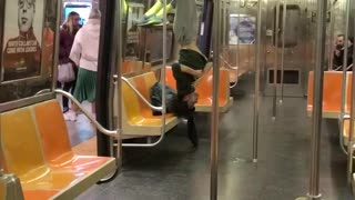 Guy in grey sweats hanging upside down on subway