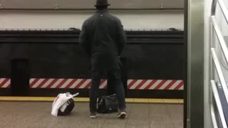 Fedora man does stretches in subway terminal while waiting for 456 train