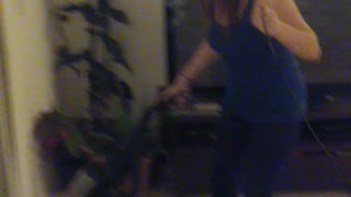 Woman Rides Electric Hoverboard While She Vacuums The House