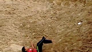 Kid in red shirt black pants backflip fail onto dirt - Video