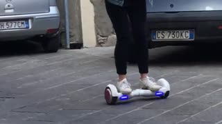Girl on white hoverboard fail purple wheels