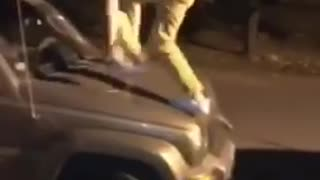 Guy jumps onto jeep and then falls onto black car and falls onto ground - Video