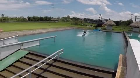 Guy wakeboard obstacle course pulled by rope faceplants off ramp into water