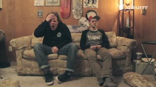 Guy sits on couch and gets exercise ball thrown at his face  - Video