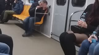 Drunk guy on subway train falls down into his seat and looks dazed